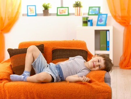 lay down: Cute little kid relaxing on sofa at home, smiling at camera.