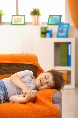 Little boy having nap, smiling in his sleep on couch in living room. photo