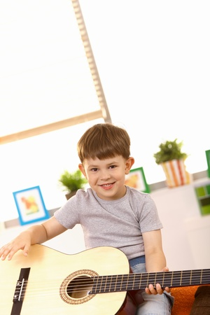 Happy five year old boy playing with guitar at home, laughing, looking at camera. photo