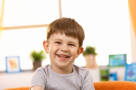 only boys: Happy little kid laughing at home, closeup portrait.