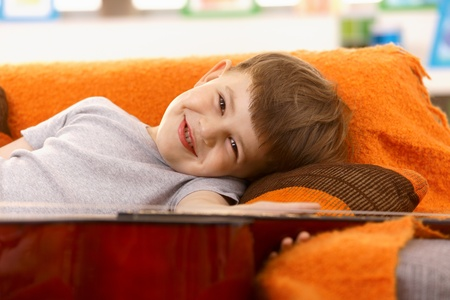 Small boy happy with guitar, lying on couch, smiling at camera. Stock Photo - 8748165