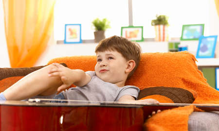 Cute little boy thinking on couch, pulling face, looking up. photo
