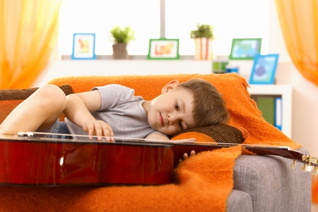 concentrating: Little boy examining guitar while lying on sofa, concentrating. Stock Photo