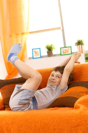 living room boy: Little kid posing on sofa, arms and legs raised, pulling face. Stock Photo