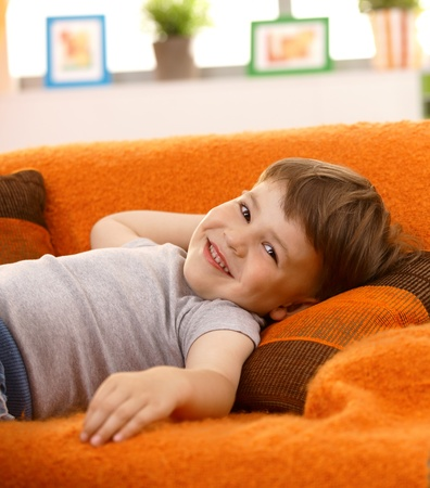 recreation room: Cute little boy lying on couch at home, laughing, looking at camera. Stock Photo