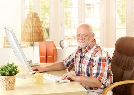 Happy senior man using computer at home, smiling at camera. Stock Photo - 8748098