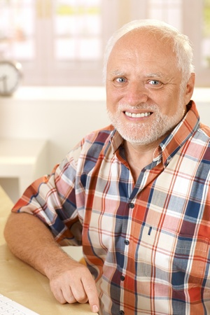 Portrait of smiling senior man sitting at home, looking at camera. photo