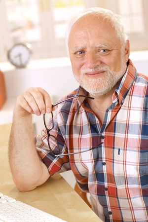 Portrait of happy older man smiling at camera, holding glasses. photo