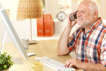Senior man talking on cellphone, using computer, smiling, looking at screen at home. photo