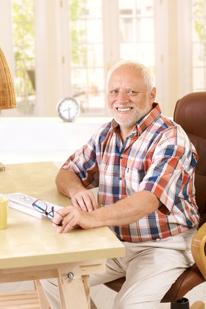 only senior men: Portrait of elderly man sitting in study at home, smiling at camera.