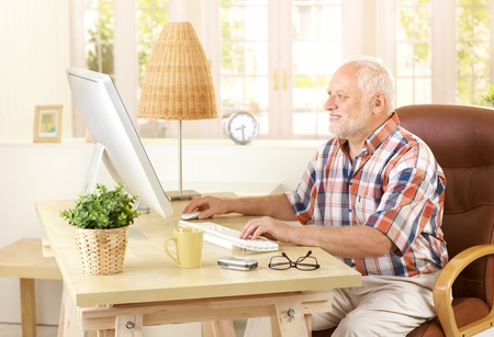Senior man using desktop computer at home, looking at screen, smiling.