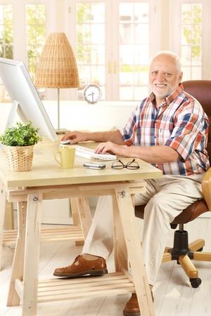 Portrait of elderly man sitting at desk using desktop computer, smiling at camera. photo