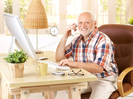 retirement homes: Happy old man on landline call sitting at desk using, computer, smiling, looking at camera. Stock Photo