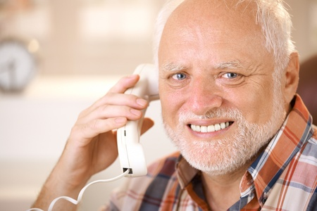 Closeup portrait of smiling senior man using landline phone, looking at camera. photo