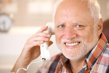 camera phone: Closeup portrait of smiling senior man using landline phone, looking at camera.