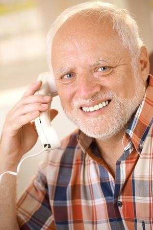 Portrait of older man on landline phone call, smiling happily at camera.