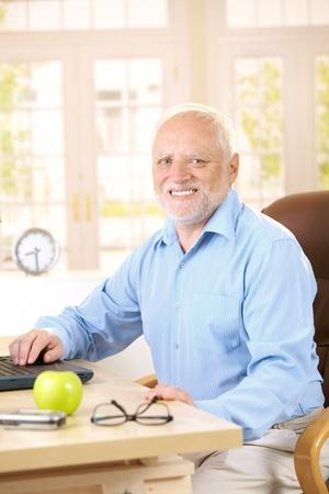 Portrait of senior man sitting at desk at home, using laptop computer, smiling at camera. photo