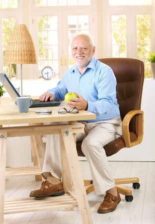Older man working in his study at home, using computer, holding apple, looking at camera, smiling.