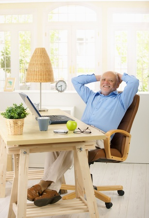 Portrait of cheerful old man in his study sitting relaxed at desk with hands on nape, looking at camera. photo