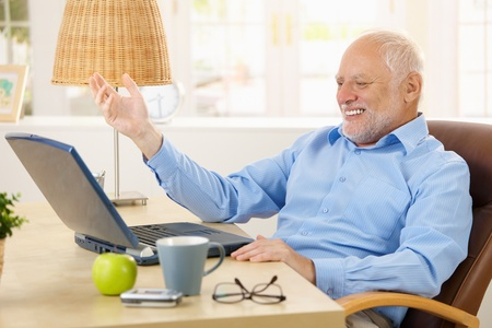 Laughing old man using laptop computer at home, looking at screen, gesturing. photo