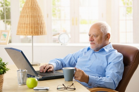 Elderly man using laptop computer in his study at home, having coffee, looking at screen. photo