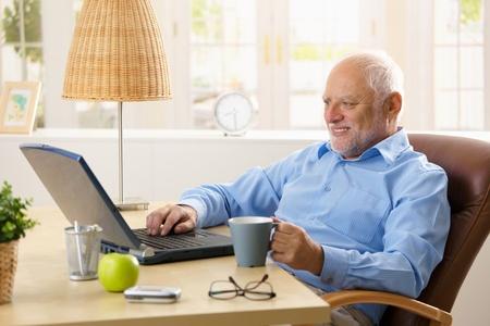 only one senior: Smiling senior man using laptop, typing on keyboard, holding coffee mug at home.