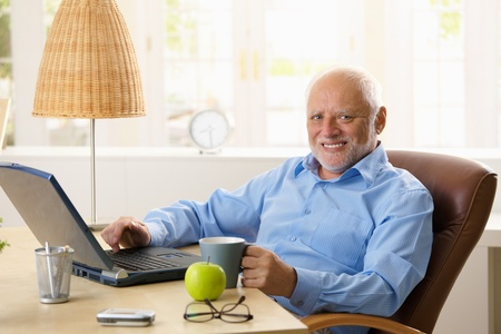 Portrait of happy senior man sitting at desk using laptop computer at home, smiling at camera. Stock Photo - 8748153