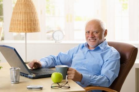 Portrait of happy senior man sitting at desk using laptop computer at home, smiling at camera. photo