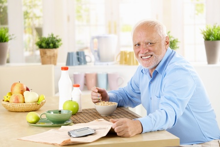senior eating: Cheerful healthy senior man having cereal for breakfast in kitchen, smiling at camera. Stock Photo