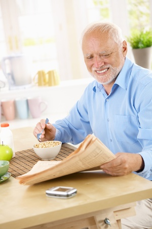 Smiling senior man sitting in kitchen reading papers while having cereal for breakfast. photo