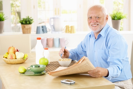 Portrait of healthy senior sitting in kitchen at breakfast, holding newspaper, looking at camera, smiling. photo