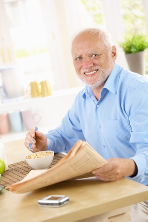 Portrait of older happy man at breakfast table, having cereal, reading papers, smiling at camera. Stock Photo - 8748150