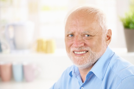 one mature man only: Closeup portrait of cheerful pensioner smiling at camera.