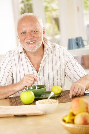 Portrait of older man having morning tea in kitchen, looking at camera, smiling. photo