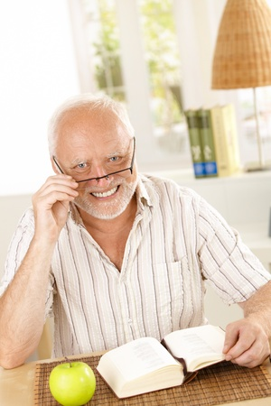 Portrait of laughing senior looking at camera, sitting with book at table. Stock Photo - 8748139