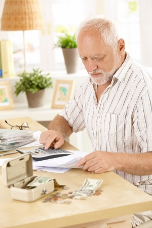 Active pensioner doing financial work at home, using calculator, looking at bills. photo