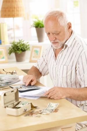 financials: Active pensioner doing financial work at home, using calculator, looking at bills.