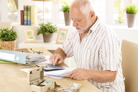 financials: Senior man busy doing calculation, counting money and bills at home, sitting at desk. Stock Photo