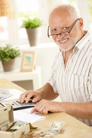 financials: Portrait of senior man wearing glasses, doing financial work at home, smiling at camera. Stock Photo