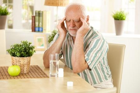 personas tomando agua: Senior hombre sentado a la mesa, tener dolor de cabeza mala, muecas, tomando la medicina. Foto de archivo