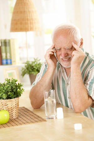 painkiller: Pensioner suffering from migraine, holding head with closed eyes, taking painkiller at home.