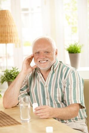 Smiling senior holding medication, sitting at table at home, looking at camera. Stock Photo - 8748778