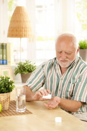 tomar: Senior man sitting at table, taking medication with glass of water at home.