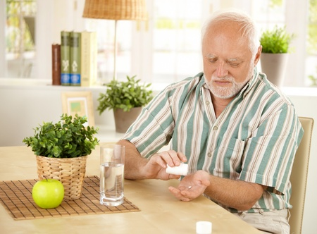 Elderly man taking pill at home, sitting at living room table. photo