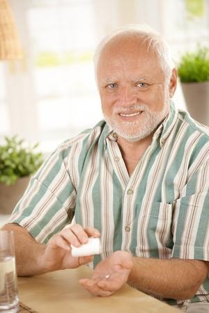 Smiling senior taking medication, looking at camera. photo