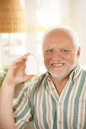 Smiling older man presenting medication, holding up phial, looking at camera, copy space. photo