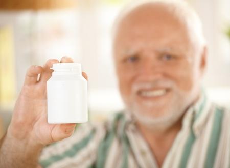Blank medicine phial in focus handheld by elderly smiling man, copyspace. photo