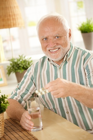 Portrait of senior man taking medicine at home, smiling at camera, holding bubble package. photo