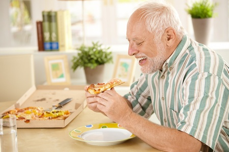 Smiling older man eating pizza slice sitting at living room table. Stock Photo