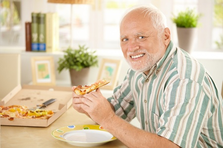 Portrait of senior man having pizza slice at home, smiling at camera. photo